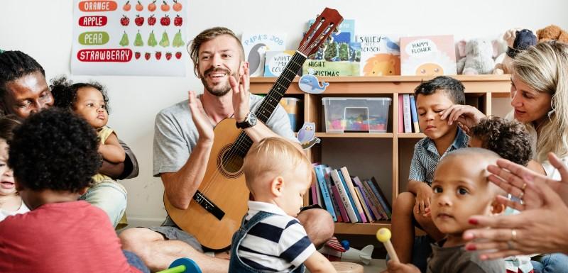 Professeur de musique qui tape dans ses mains, la guitare sur les genoux