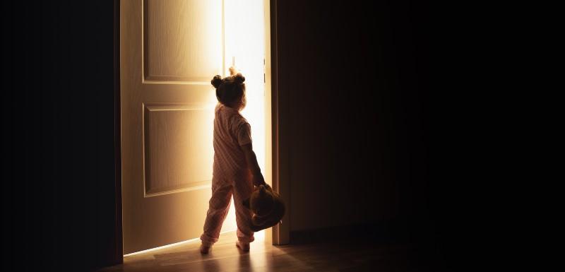 Petite fille qui ouvre la porte pour aller vers la lumière, son nounours à la main